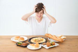 食べ物の前で頭を抱える女性