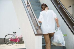 買い出しの荷物を持って階段を上がる女性