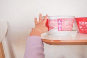 カップ麺に伸ばす子どもの手